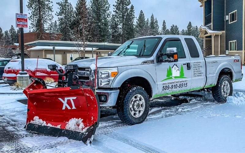 A Spokane's Finest Lawns gray work truck outfitted with a commercial snow plow.