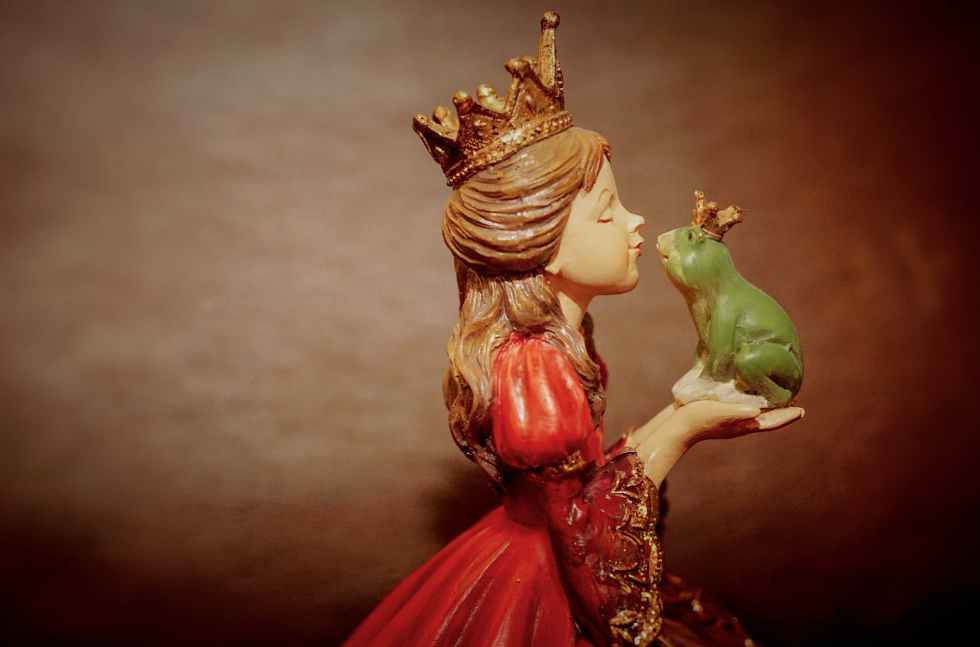 woman wearing crown holding frog figurine
