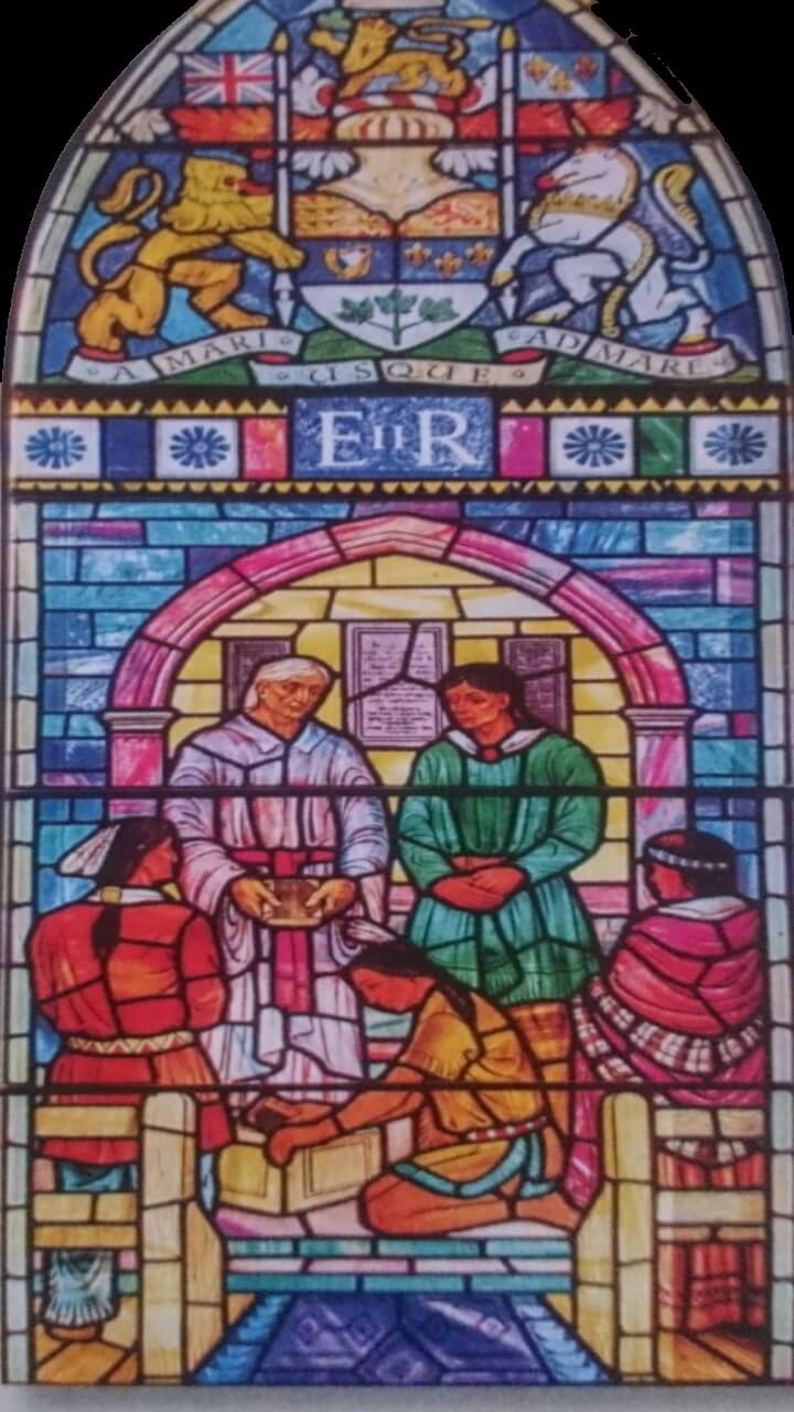 A stained glass window in the Royal Mohawk Chapel, featuring five Indigenous figures, one of whom is John Norton holding the gospel he translated