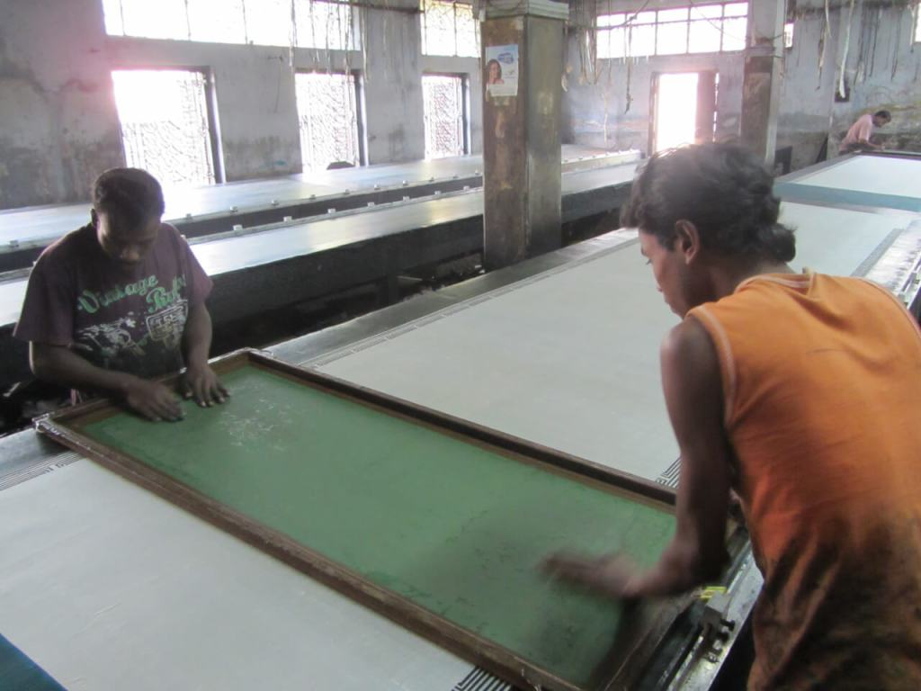 Workers at a Craft Resource Center-associated workshop in India prepare to paint silk using a patterned screen