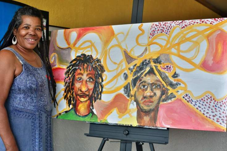 Loretta Day of ROHO Collective poses next to her artwork. ROHO is an 501(c)3 Arts Organization that supports artists of color. Each artist has has their own genre of art and creativity.