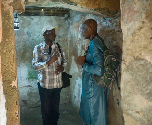 A guide explaining to Floyd the significance of a room in the slave quarters on Goree Island