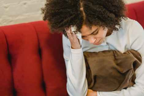 young african american miserable woman touching head on couch