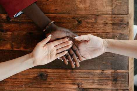 diverse women stacking hands on wooden table