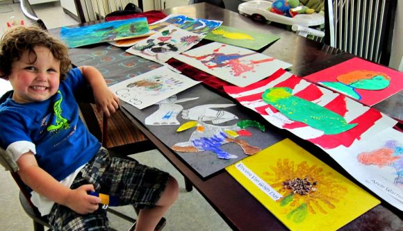 Caleb, in the summer of 2011, showing off all his artwork from camp.