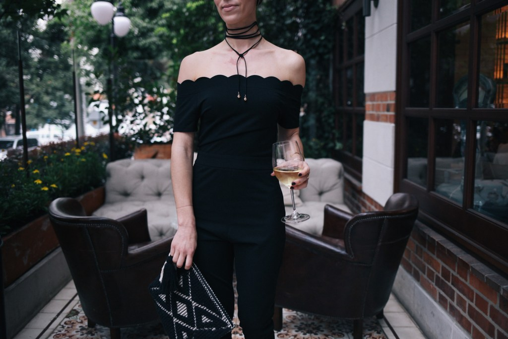 Blogger Mary Krosnjar wearing scalloped jumpsuit from Shein and Sole Society tasseled woven clutch