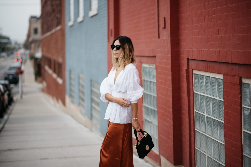 Blogger Mary Krosnjar wearing H&M Rust Satin Skirt and white oversized blouse