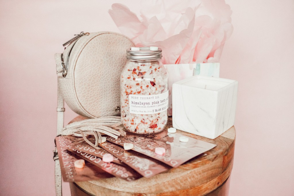 Himalayan bath salts, rose face masks, marble candle and beige circle crossbody bag