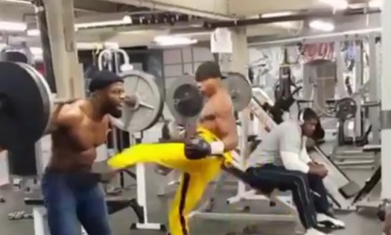 Man Lifting Weights While Being Punched and Kicked in the Abs