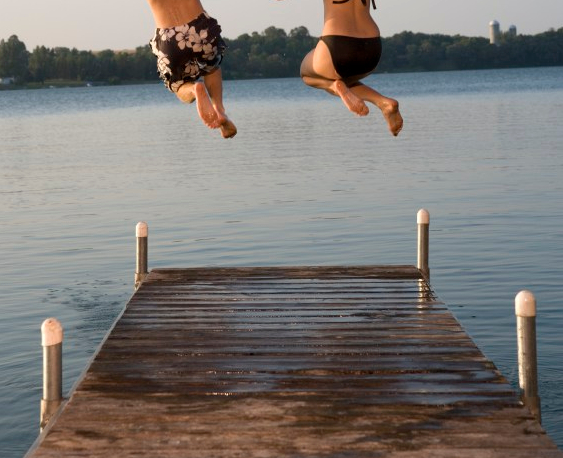 Sport & Social Group team members jumping into a lake