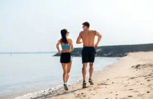 couple in sports clothes learns to avoid ankle injuries while running along on beach | Muir Orthopaedic Specialists | Walnut Creek, CA
