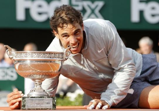 Rafael Nadal of Spain bites the trophy as he poses during the ceremony after defeating Novak Djokovic of Serbia during their men's singles final match to win the French Open Tennis tournament in Paris