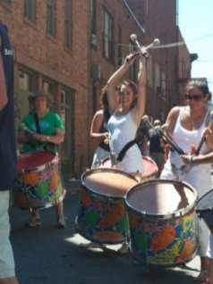 One Troy Samba member is thrilled to take a quick break between pieces during a performance at Troy River Fest on Saturday, June 18.