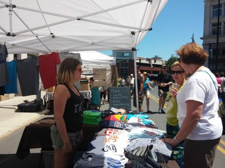 Attendees stop to look at T-shirts designed and printed by Troy Cloth & Paper during River Fest on Saturday, June 18.