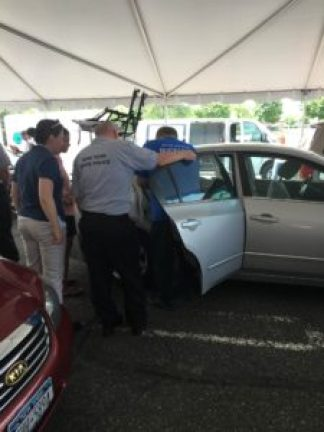 Bill VanAlstyne checks out a car at the seminar to make sure the seatbelt and car seat are installed correctly.