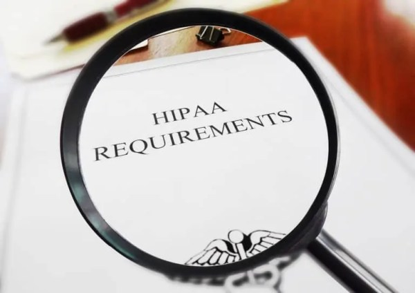 HIPAA healthcare requirements document with magnifying glass