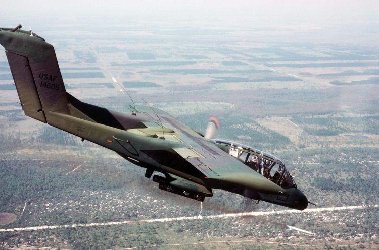An air-to-air right side view of an OV-10 Bronco aircraft firing a White phosphorus smoke rocket to mark a ground target. The aircraft is used by forward air controllers in support of ground troops. Photo from November 84 Airman Magazine. Service Depicted: Air Force Camera Operator: TSGT BILL THOMPSON - ID:DFST8505744