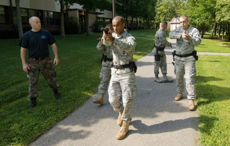 A Massachusetts State Police Special Tactical Operations Team monitors as Senior Airman Mark Cayer, Airman 1st Class Ronald Ashley, Airman 1st Class Edwin Torres and Senior Airman John Reed to learn methods for neutralizing an active shooter Aug. 6 at Hanscom Air Force Base, Mass. Massachusetts State Police Special Tactical Operations Team members educated Airmen on moving into and within the threat space using a diamond formation, where each member of the four-man team monitors a quarter of the 360-degree view around them. The Airmen are assigned to the 66th Security Forces Squadron. (U.S. Air Force photo/Rick Berry)
