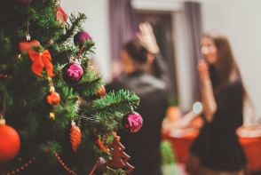 This picture represents the holiday season with a Christmas tree and party.