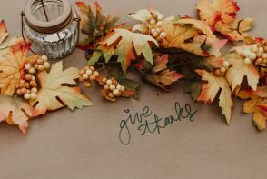 Fall leaves and the words 'give thanks,' used for decoration in preparation for the holiday season.