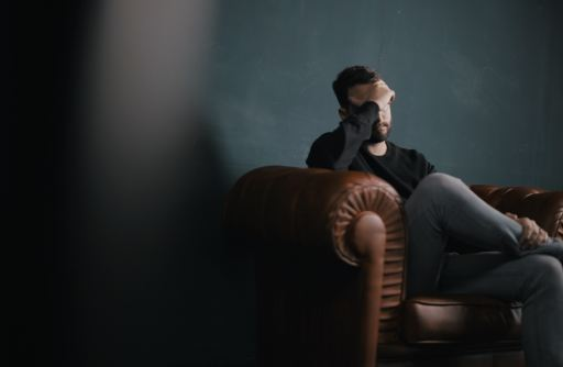 Man in chair appearing to be stressed or worried.