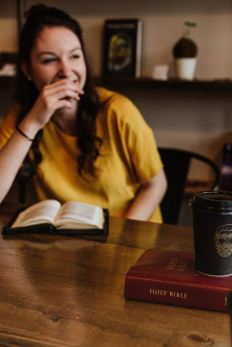 Woman with yellow-gold top sitting at a table with a bible another book and a cup of coffee. Photo represents the the integrity of our words lead to a life of joy.