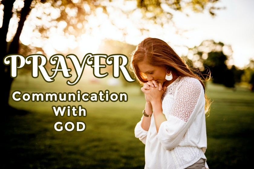 Caucasian woman standing with head bowed and hands claps together, surrounded by nature. Photo represents Prayer--Communication with God.