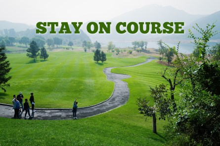 Photo of people standing on a paved road winding through a lush green meadow. Pic represents how one should follow God's directions and Stay On Course.