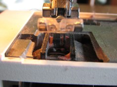 With the throat plate removed, I can see where there is lint built up on my machine. I can dust it out