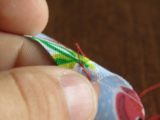 It should look something like this. You can clip your threads close, but be cautious to leave a small tail on either side.