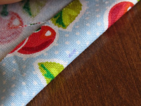 With the seam I marked before, I flip my fabric over so the right side (the printed side) is facing down. Then I fold my marked edge back, just until I can see the marks I made with my marking pen.