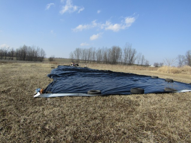 After we unrolled and unfolded the tarp, we needed to weigh it down and straighten it out. DO NOT try attempting to do this on a windy day. We did this on a pretty calm day and it still caught a mild wind a few times and was difficult to control.