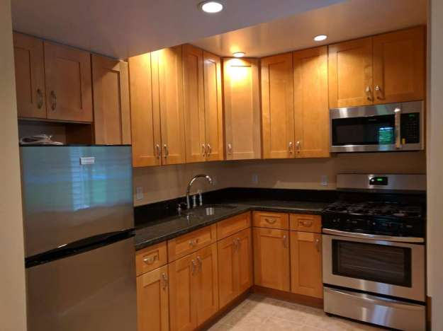 Upgrade kitchen with stainless steel refrigerator and stove. Light brown kitchen cabinets.