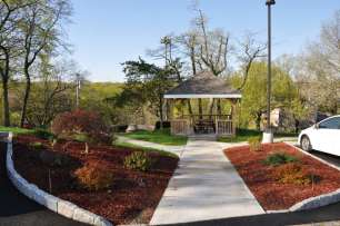 Gazebo walkway landscaped with red mulch and shrubs.