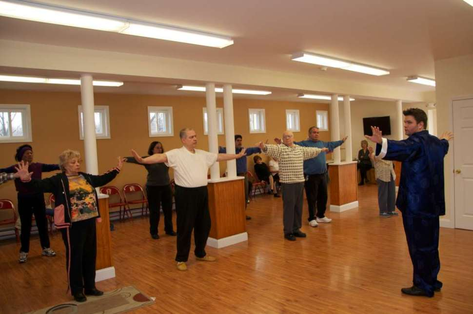 Male Tai Chi instructor in front of residents.