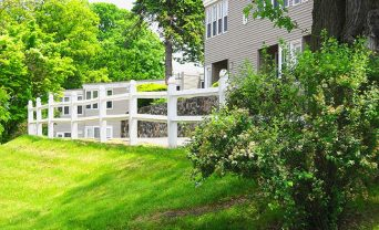 White picket fence along path behind Apartment 9.