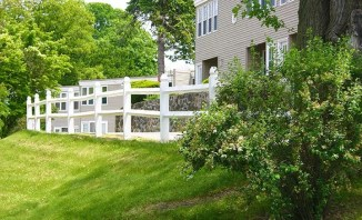 White picket fence along path behind apartments.