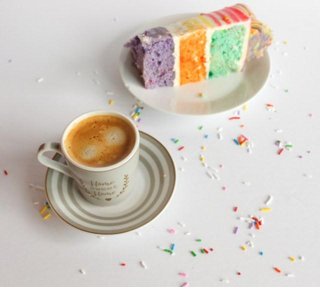 Rainbow striped cake slice with coffee