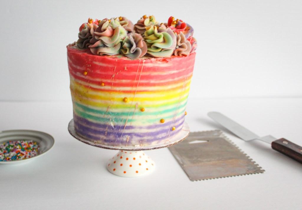 Rainbow striped cake with cake tools.