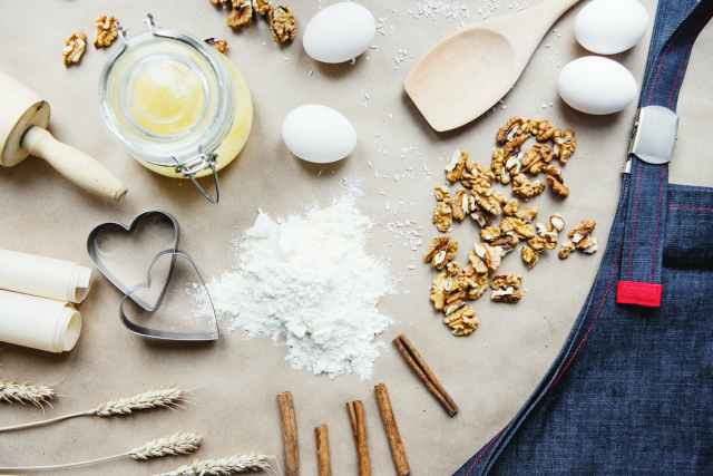 composition of baking ingredients with apron in kitchen