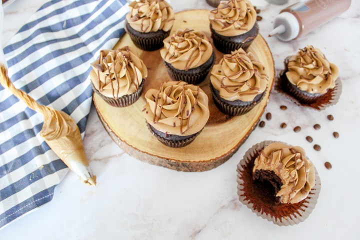 mocha cupcakes topped with coffee buttercream on a tray with coffee buttercream in piping bag on the side