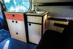 Sliding door cabinet, sink cabinet, hot water tank (next to bench seat)