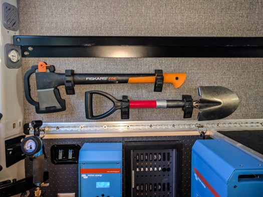 Axe and shovel mounted under bed rail on inside wall of van using Quick Fist clamps.
