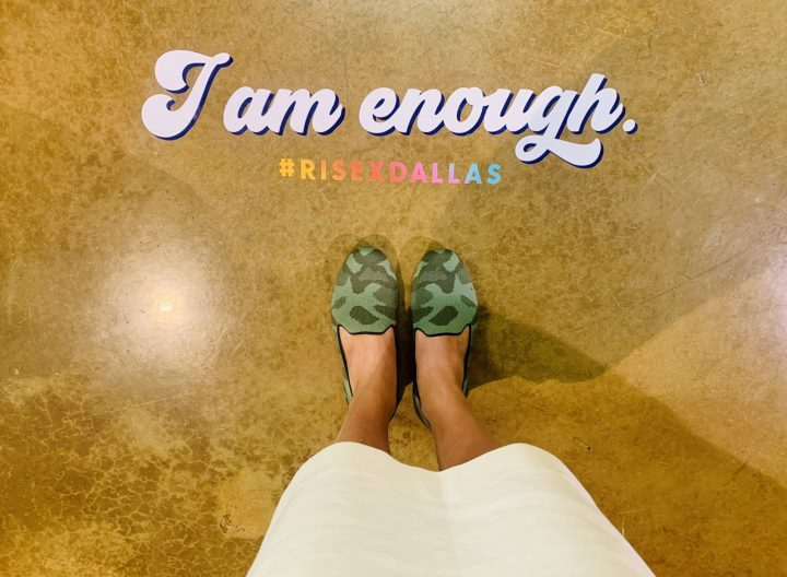 "A photo of a sticker on the floor reading "" I am Enough"" #RiseDallas Also a pair of #Rothys camo colored standing infront of the sign. More inspiring posts can be found at www.sprouting-vitality.com #sproutingvitality #mckenzieonthemove"