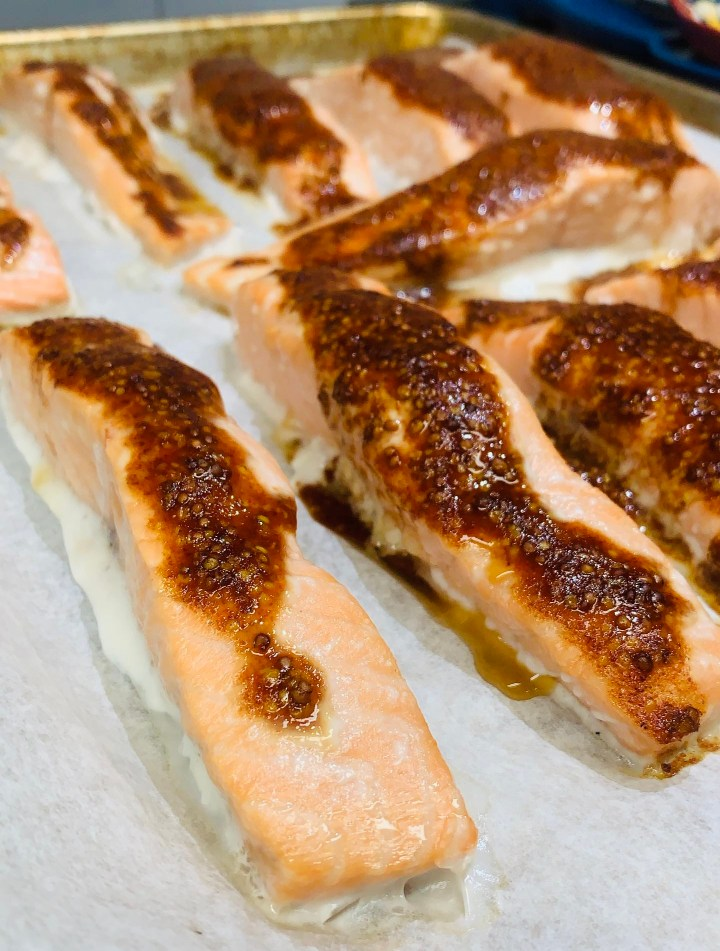 Chili Dijon Maple Salmon right out of the oven, perfectly cooked. This recipe brings together the perfect amount of spice and sweetness to heighten the flavors of the salmon. For more food recipes and travel posts be sure to follow me at www.sprouting-vitality.com or on instagram @sproutingvitality. #kenzinthekitch #mckenzieonthemove