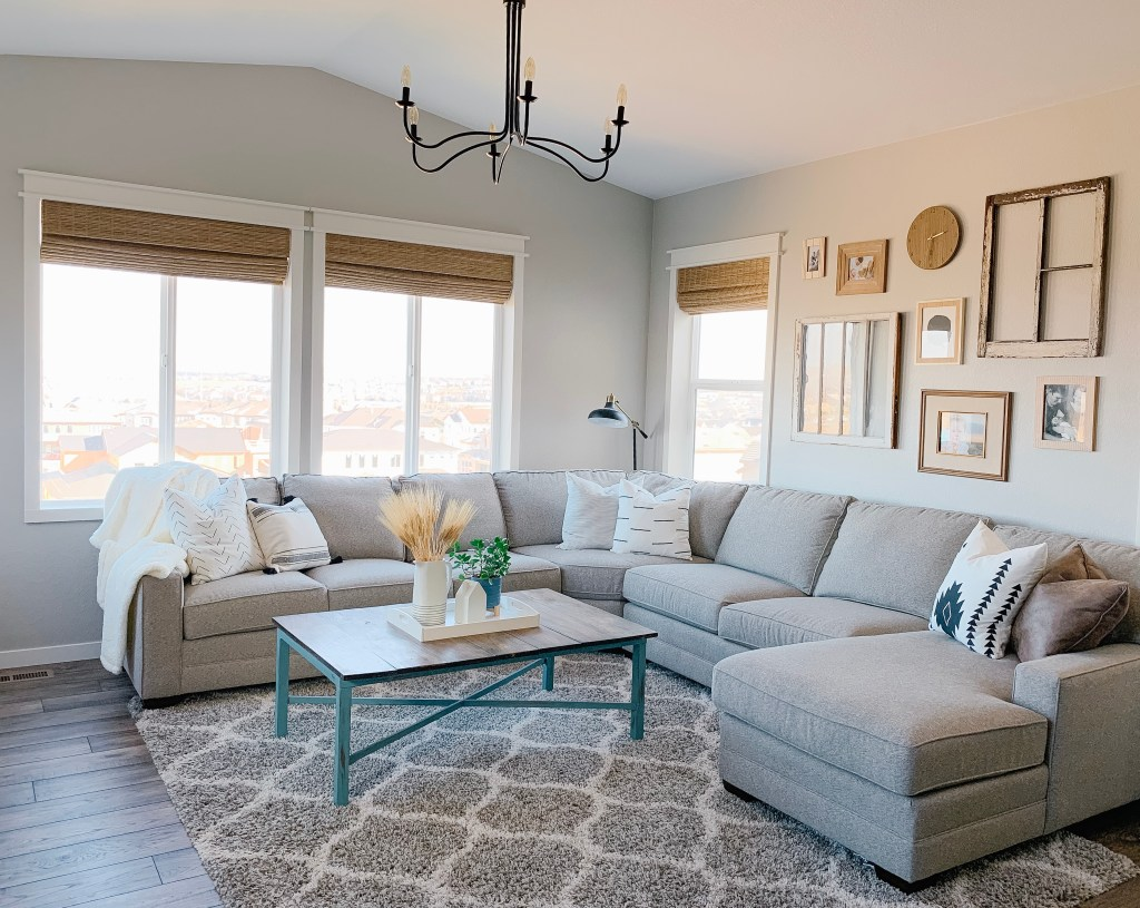 Living room with window casing and woven roman shades. Also has a fireplace, plants, a sectional gray couch and is painted gray.