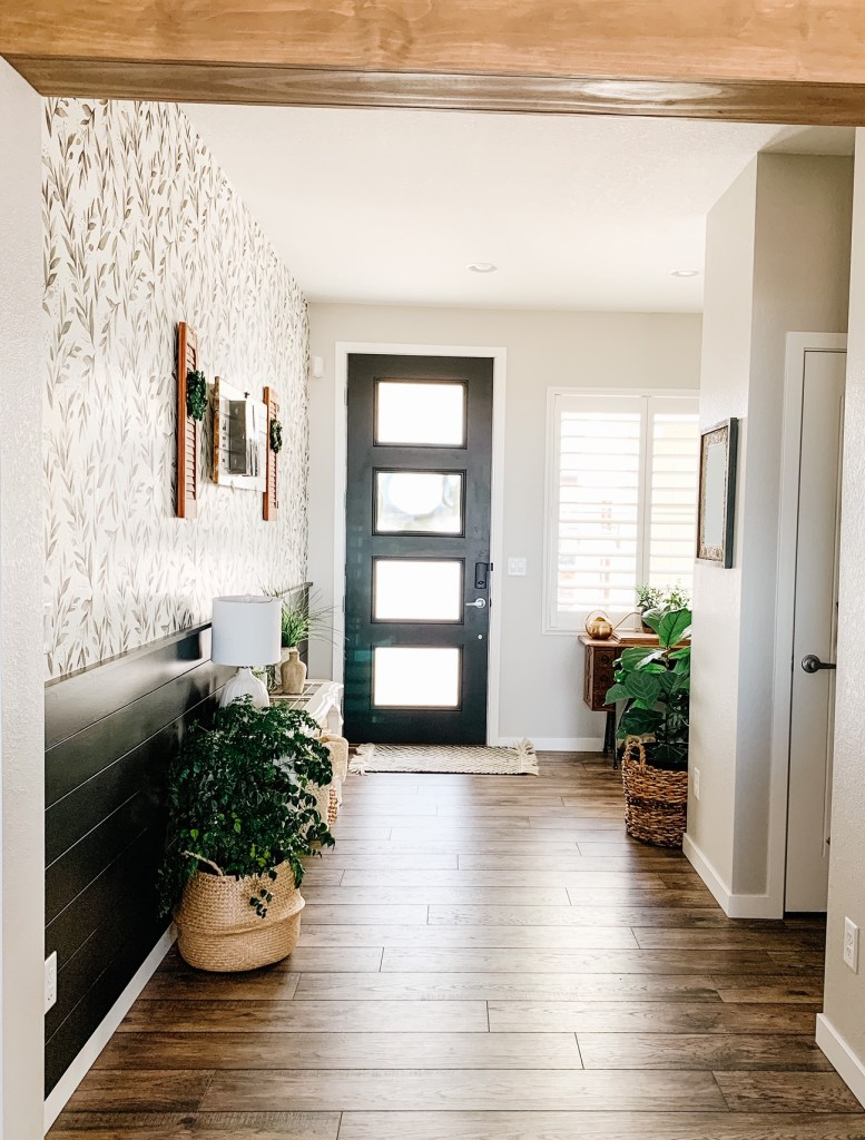entryway with olive branch peel and stick wallpaper and an entry table and plants