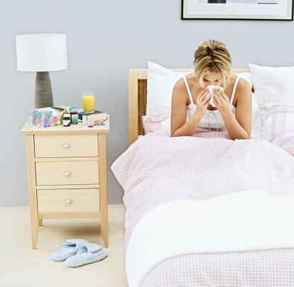 sick-woman-sneeze-bed