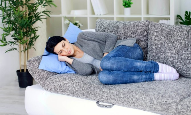 Woman with stomach pain lies down