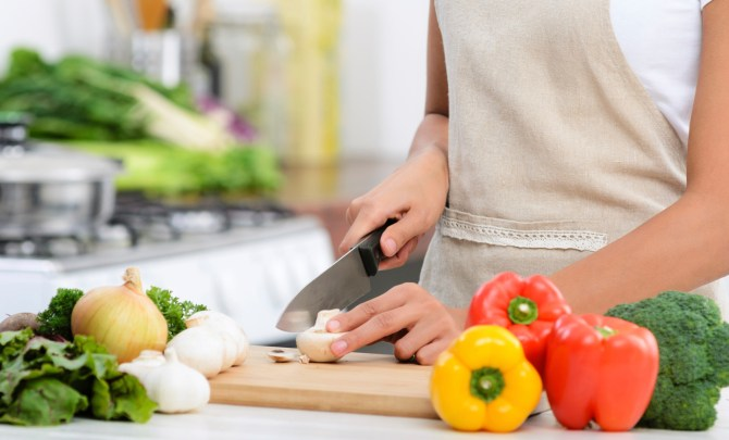 Woman cutting vegetables in kitchen.